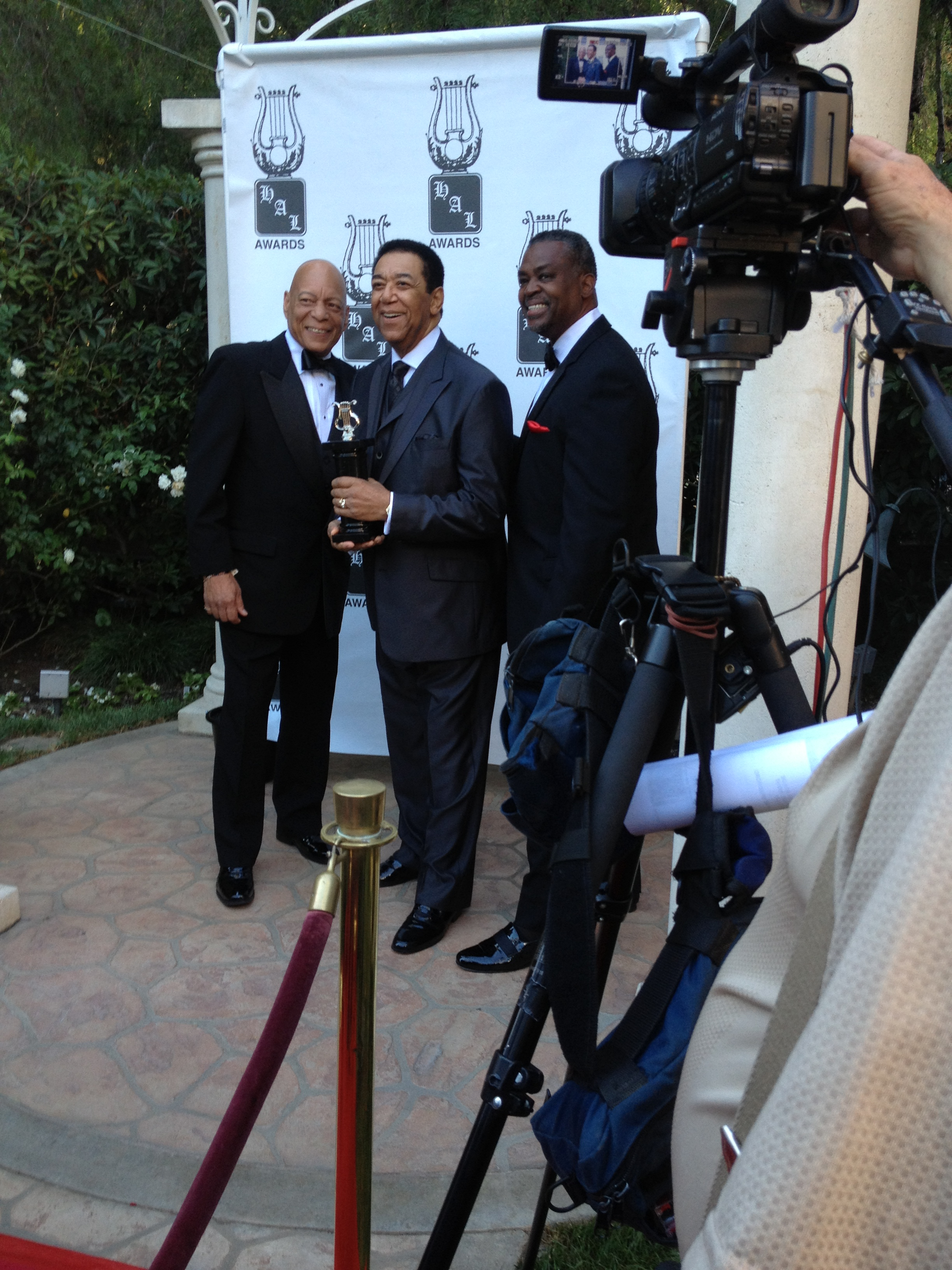Terry holding his award on the press red carpet with Stan and Starling.